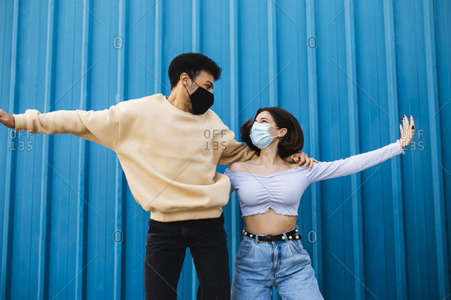 Carefree couple wearing face mask dancing while standing against blue wall