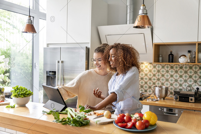 Smiling female colleagues in office kitchen watching food recipe on tablet
