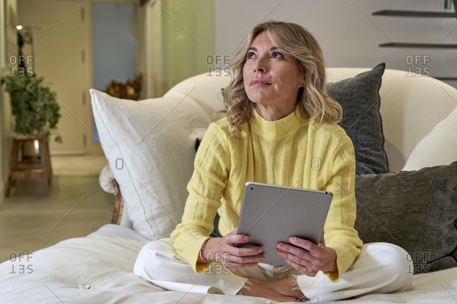 Fashionable mature woman day dreaming while holding digital tablet at home