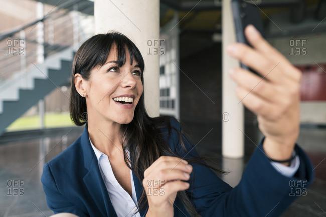 Smiling female entrepreneur doing video call through smart phone in lobby