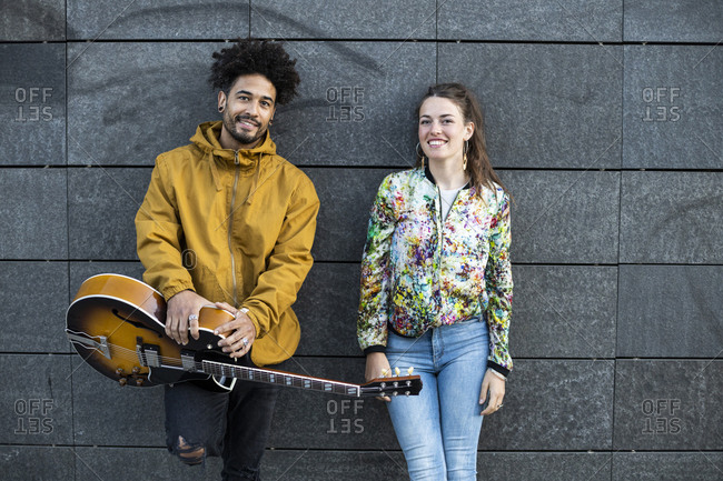 Smiling man holding .guitar while standing by woman against concrete wall