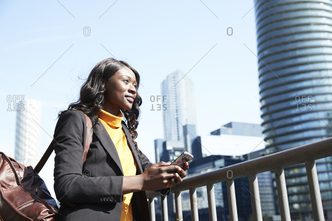 Smiling businesswoman looking away while standing by railing on sunny day