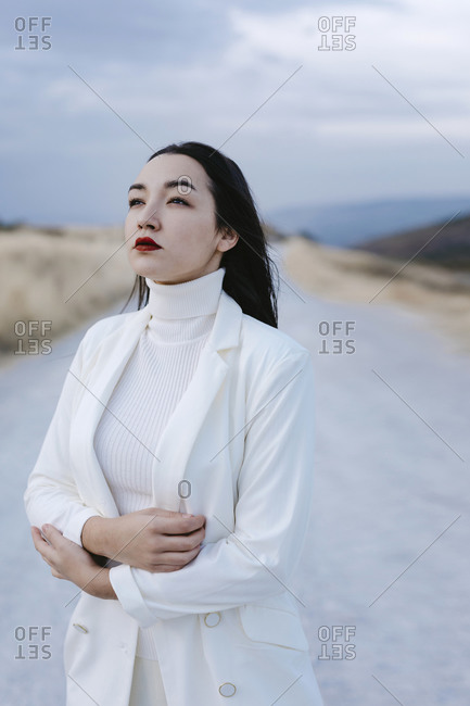 Thoughtful woman wearing white jacket looking away while standing on road