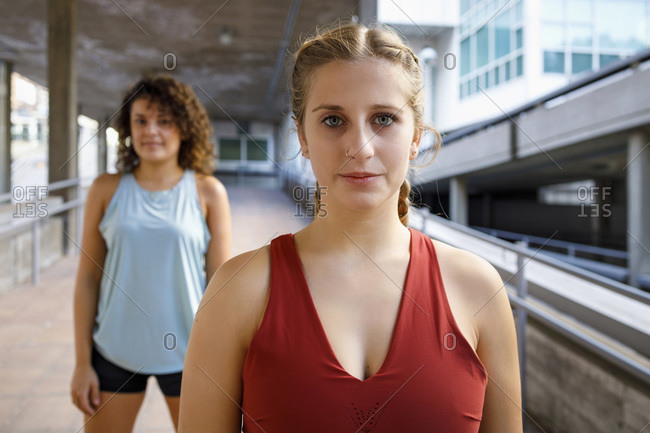 Young athlete staring while standing with friend in background on bridge