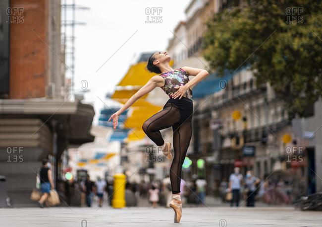 Dancer practicing ballet dancing while standing tiptoe on street in city
