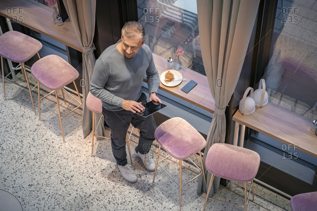 Businessman using digital tablet while standing by window at modern cafe