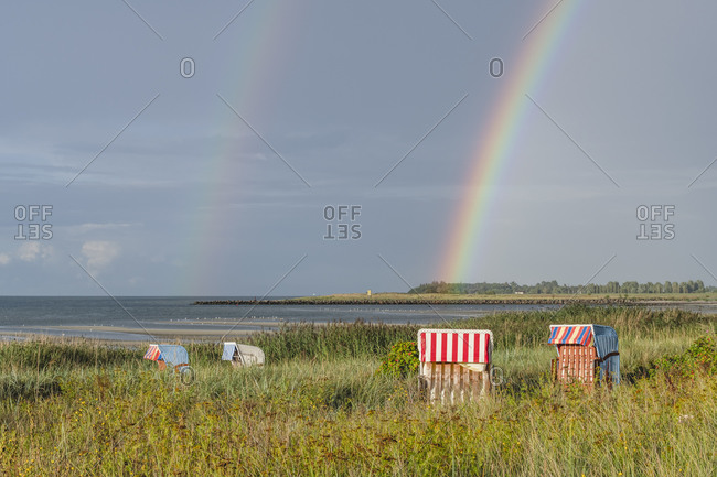 Double rainbow arching over hooded beach chairs standing on grassy shore