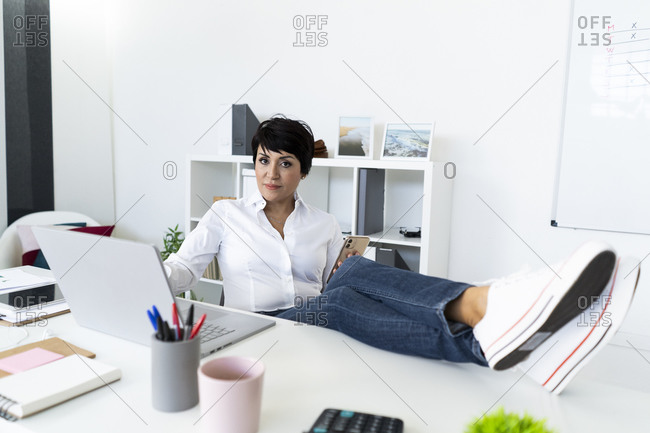 Portrait of businesswoman taking break with smart phone at office table