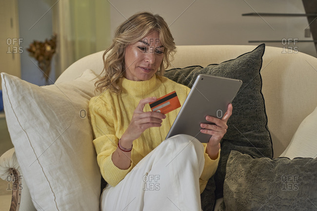 Fashionable woman paying by credit card while online shopping from home