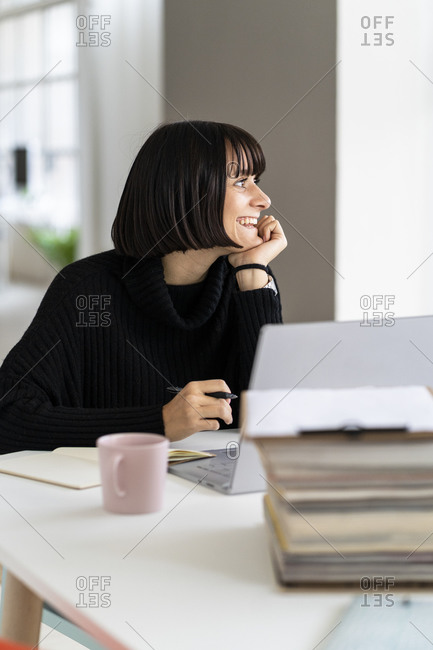 Smiling young female student day dreaming while studying in study room