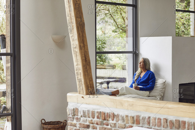 Thoughtful mature woman with coffee cup looking through window at home