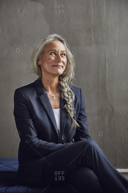 Female entrepreneur with braided hair against gray wall at home office