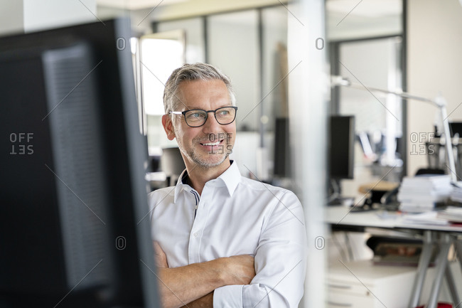 Smiling male professional with arms crossed day dreaming at work place