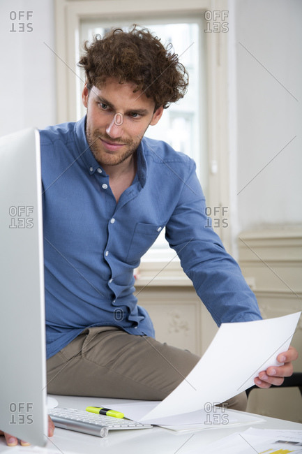 Young businessman working on computer with document at desk in office