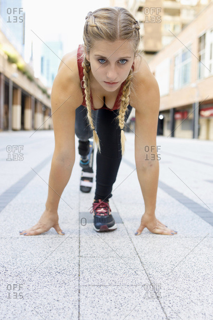 Young woman with prosthetic leg crouching for sports race on footpath