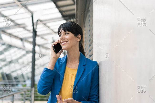 Businesswoman talking on mobile phone while leaning by wall at office