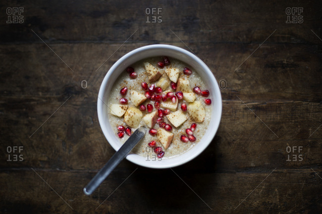 Porridge with apples- cinnamon and pomegranate seeds in bowl on table