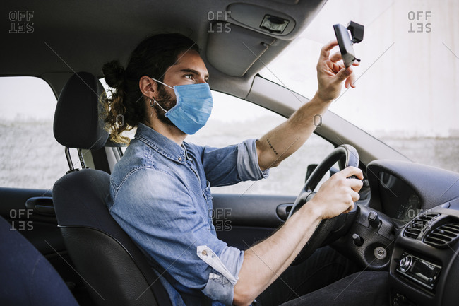 Young man wearing protective face mask while adjusting mirror in car