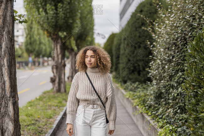 Beautiful young woman looking away while walking on footpath in city