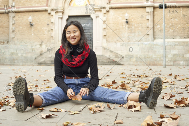 Smiling woman playing with fallen dry leaf while sitting on footpath