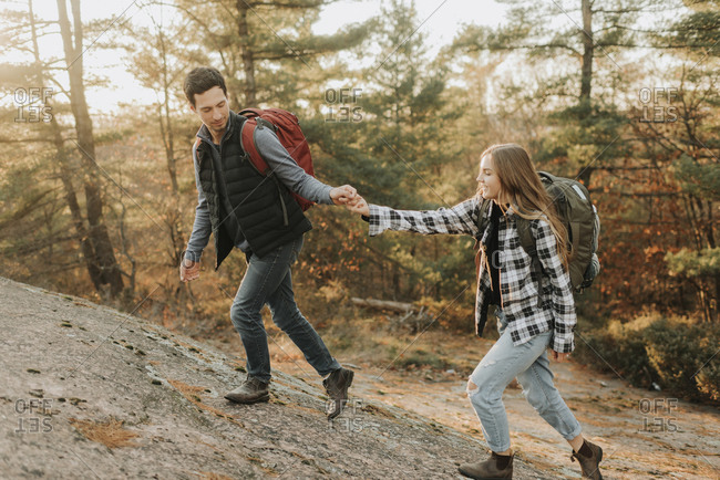 Young couple holding hands while walking up hill during autumn hike