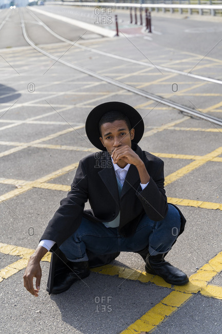 Stylish young man wearing hat crouching on street during sunny day