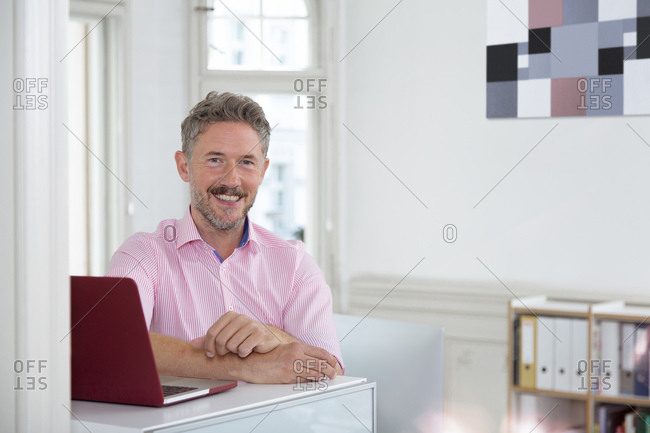 Smiling mature male professional by laptop at desk in office cabin