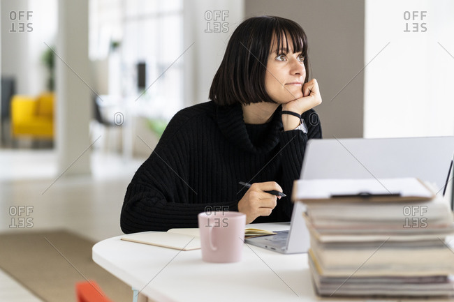 Thoughtful female student with hand on chin studying in study room