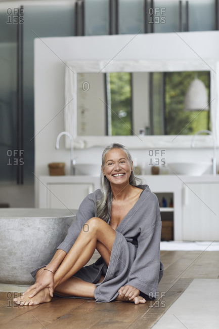 Happy mature woman looking away while sitting on floor by bathtub