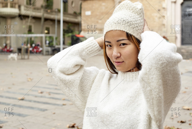 Beautiful woman wearing knit hat while standing on street in city