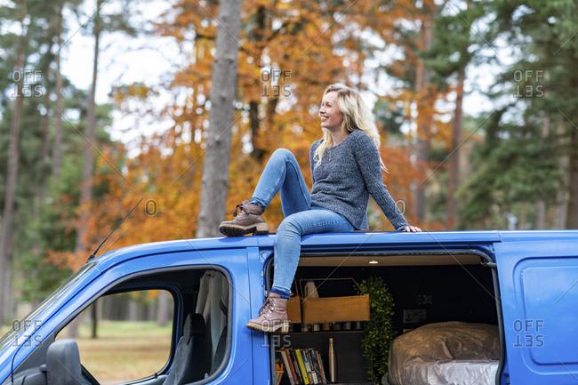 Smiling woman looking away while sitting on rooftop of camper van