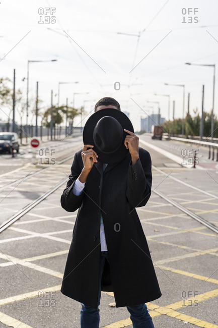Young man covering face with hat between railroad track on street