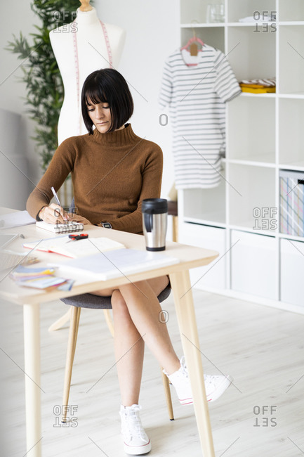 Female fashion designer working on new designs at desk in studio