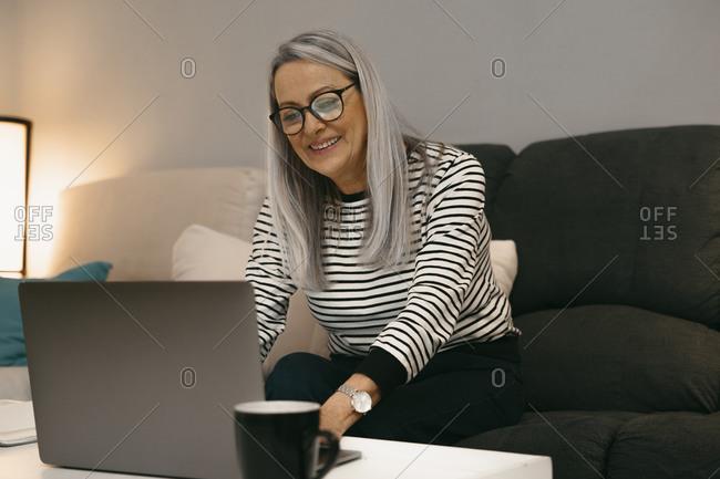 Smiling senior woman using laptop while sitting on sofa at home