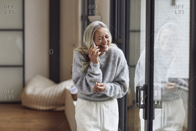 Laughing mature woman with eyes closed talking on phone at home