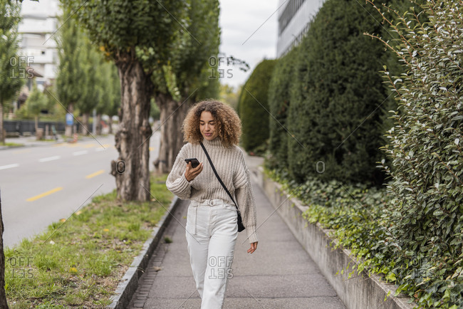 Young woman using smart phone while walking on footpath in city