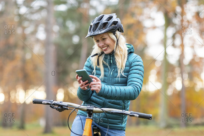 Happy woman with blond hair using mobile phone at Cannock Chase