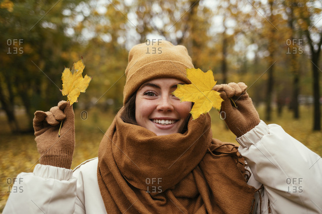 Happy young woman covering eye with autumn leaf in public park