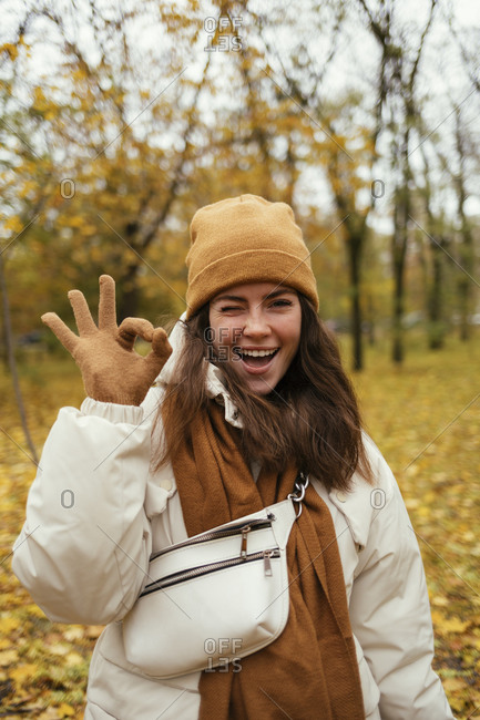Happy young woman winking while making OK sign in autumn park