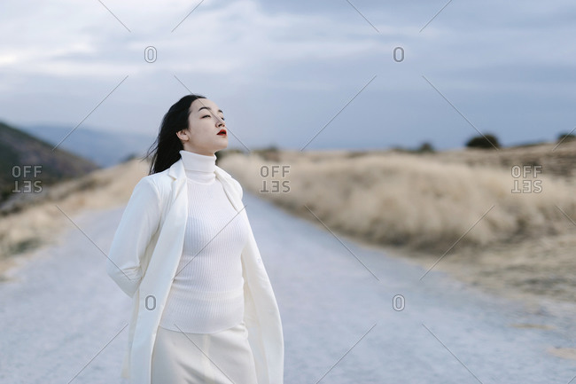Woman in white jacket standing with hands behind head on road