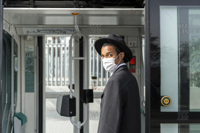 Young man in protective face mask entering tram on sunny day