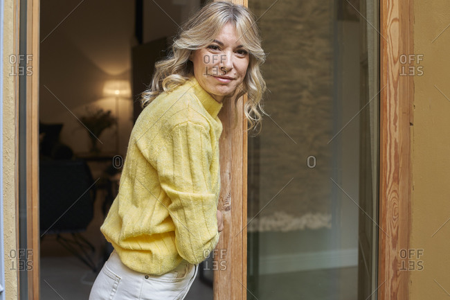 Smiling mature woman with blond hair leaning on door at home