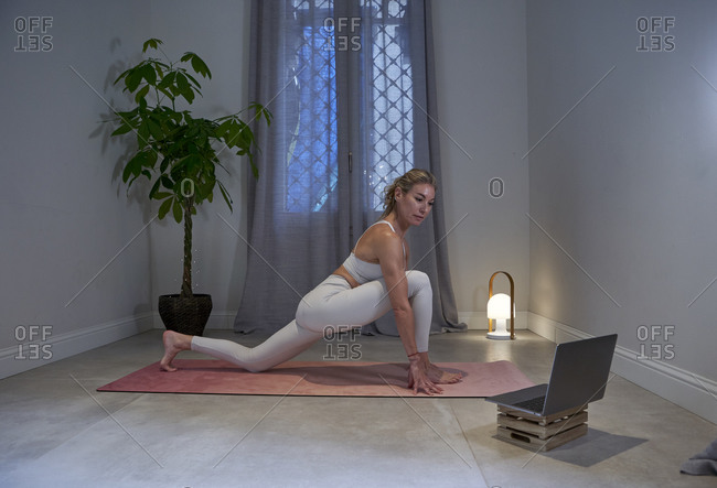 Female yoga instructor doing yoga in front of laptop at home