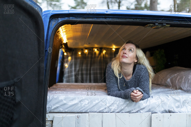 Thoughtful woman looking up while lying on bed in motor home