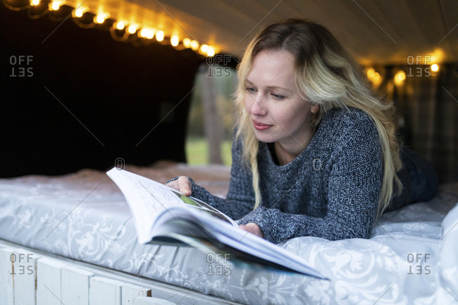 Smiling woman reading book while lying on bed in camper van