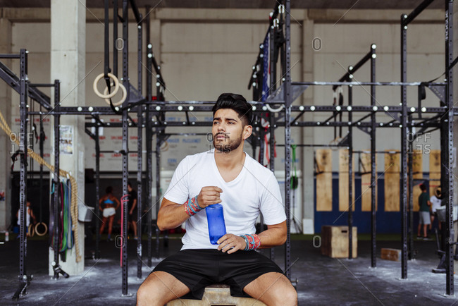 Young man holding water bottle while sitting on box at gym