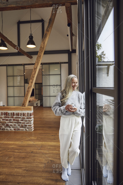 Happy woman with coffee cup leaning on glass door at home