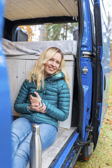 Smiling woman with tea cup sitting at door of motor home