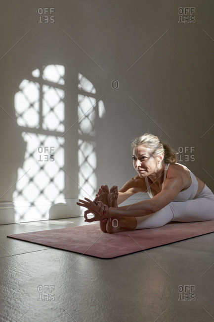 Mature woman doing yoga on mat in exercise room at home