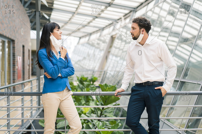 Businesswoman and male entrepreneur discussing by railing in office corridor during pandemic